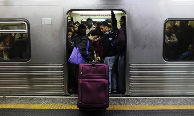 A commuter waits with her suitcase for an available train at a subway station in downtown Sao Paulo