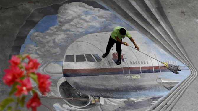 """FILE - In this April 8, 2014, file photo a school utility worker mops a mural depicting the missing Malaysia Airlines Flight 370 at the Benigno """"Ninoy"""" Aquino High School campus at Makati city east of Manila, Philippines. After the shooting down of Malaysia Airlines Flight 17 on Thursday, July 17, 2014, Malaysia is now grappling with the horrific loss of two of its airplanes, just four months apart. (AP Photo/Bullit Marquez, File)"""