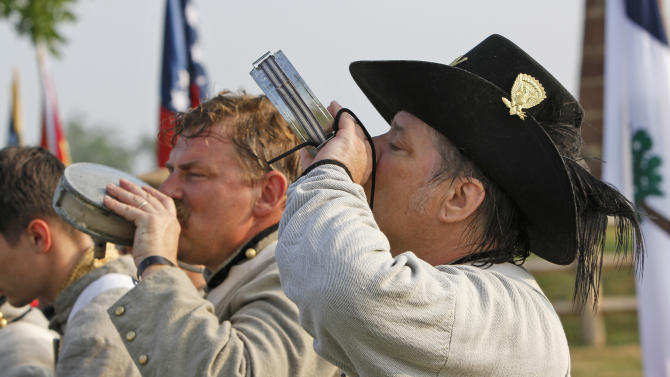 Civil War re-enactors Phil Reynolds, right, of Talmadge, Ohio, and John Zuzek, of Grant, Fla., drink from canteens as they muster to participate in the First Battle of Manassas 150th Anniversary re-enactment at the Manassas National Battlefield Park in Manassas, Va., Thursday, July 21, 2011.   The re-enactors, who pride themselves in authenticity of uniforms, will participate in a re-enactment of the battle this weekend in 100-degree heat. (AP Photo/Steve Helber)