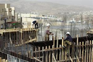 Palestinian labourers work on a construction site in …