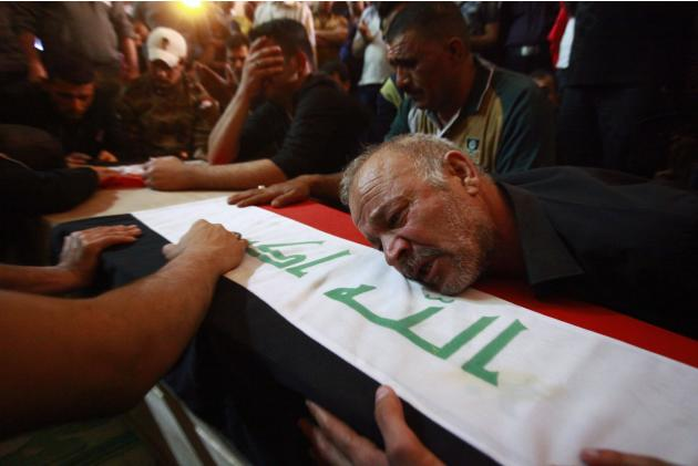 Mourners grieve near the coffin of an Iraqi SWAT trooper who was killed in clashes during his funeral, in Najaf