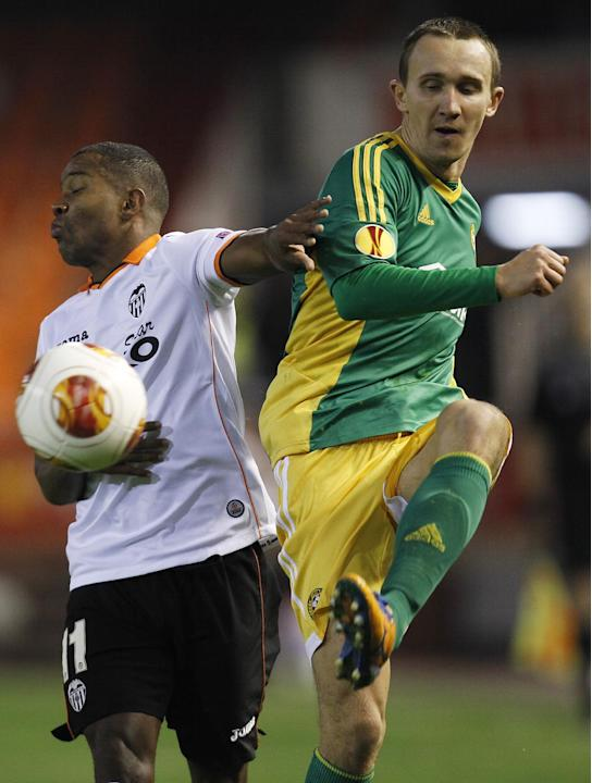 Kuban Krasnodar's Aleksei Kozlov, front, duels for the ball with Valencia's  Dorlan Pabon during their  Europa  League Group A soccer match at the Mestalla stadium in Valencia, Spain, Thursday