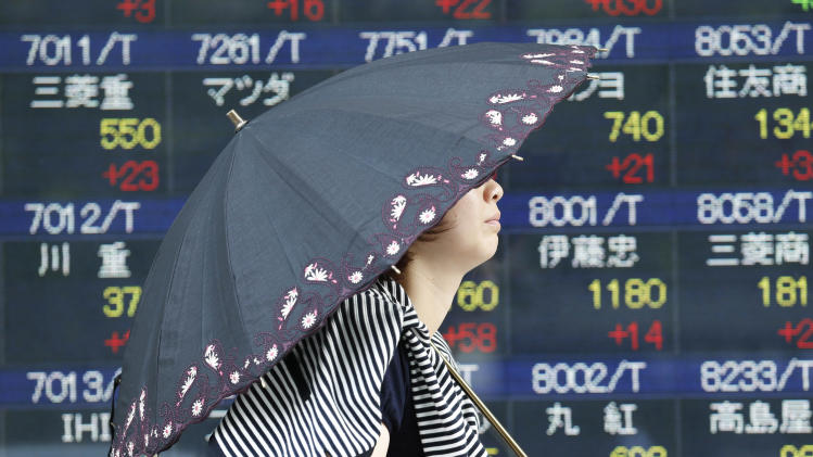 A woman walks by an electronic stock board of a securities firm in Tokyo, Thursday, Aug. 1, 2013. Asian markets rose Thursday after the U.S. Federal Reserve gave no indication it was preparing to wind down a massive bond-buying program that has propelled investors into stocks. (AP Photo/Koji Sasahara)