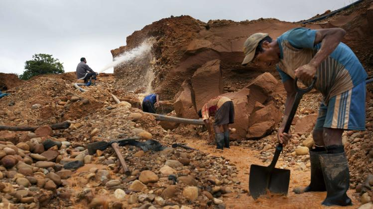 """In this May 22, 2014 photo, men mine for gold using a rudimentary technique known as """"chiquiquiar"""" in Huepetuhe in the Madre de Dios region of Peru. After a government crackdown on illegal mining companies in April, the miners who stayed behind are reduced to rudimentary gold extraction using pickaxes, shovels and small motors. (AP Photo/Rodrigo Abd)"""