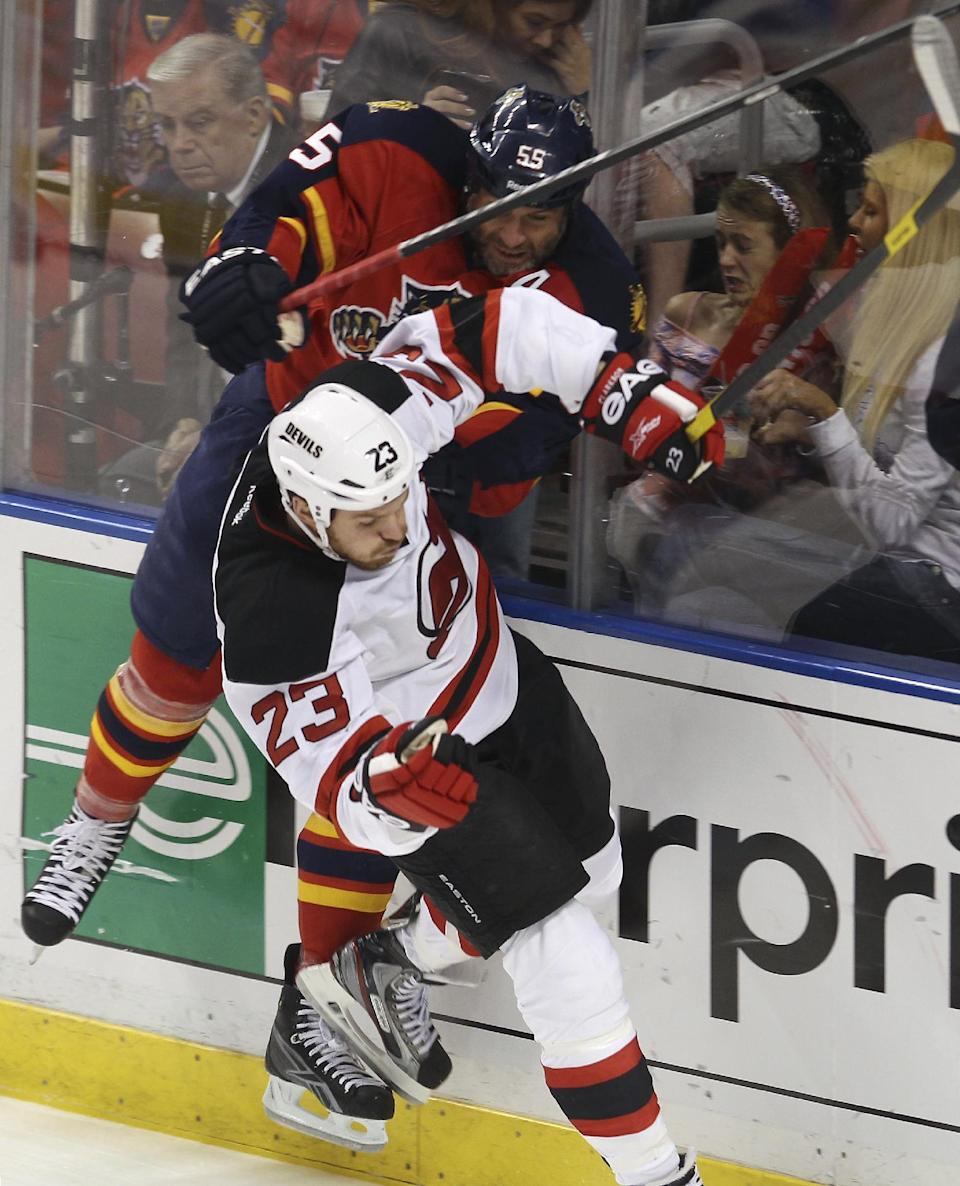 Florida Panthers' Ed Jovanovski (55) and New Jersey Devils' David Clarkson (23) work along the boards during the first period of Game 7 in a first-round NHL Stanley Cup playoff hockey series, in Sunrise, Fla., Wednesday, April 26, 2012. (AP Photo/J Pat Carter)
