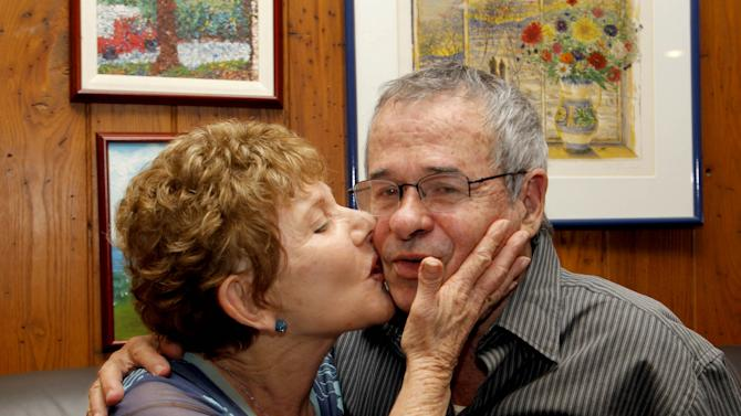 In this Wednesday Oct. 9, 2013 file photo, Tami Warshel kisses her husband, University of Southern California Professor of Chemistry and Biochemistry, Arieh Warshel, at his home in Los Angeles, after he was awarded the Nobel Prize in Chemistry. As a small country that takes special pride in the achievements of its best and brightest, Israelis were delighted with word that two of their own, Michael Levitt and Arieh Warshel, had won this year's Nobel Prize for chemistry. But the celebration was tempered by a single fact: the duo left Israel long ago for greater opportunities in the U.S. (AP Photo/Nick Ut, File)