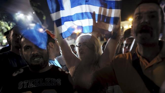 """""""No"""" supporters shout slogans and wave Greek national flags during celebrations after a referendum in Athens, Greece"""