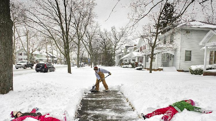 Jason Smith  clears the sidewalk in front of his home at the 2400 block of Anthony Blvd., in Fort Wayne, Ind., before heading to work Wednesday morning March 6, 2013, as his daughters Kylie Smith, right, 8, and Alexa Smith, 7, make snow angels on their day off from school.  (AP Photo/The Journal Gazette, Swikar Patel)   NEWS-SENTINEL OUT; MANDATORY CREDIT; NO SALES; MAGS OUT