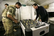 "British Prime Minister David Cameron (R) plays table football with a Royal Marine during a visit to Forward Operating Base Price in Helmand Province, Afghanistan, on December 20, 2012. During his visit, Cameron insisted that the ""high price"" paid by servicemen has been worthwhile"