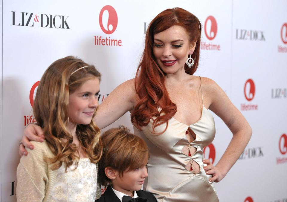 "From left, actors Taylor Ann Thompson, Trevor Thompson and Lindsay Lohan attend a dinner celebrating the premiere of ""Liz & Dick"" at the Beverly Hills Hotel on Tuesday, Nov. 20, 2012, in Beverly Hills, Calif. (Photo by John Shearer/Invision/AP)"