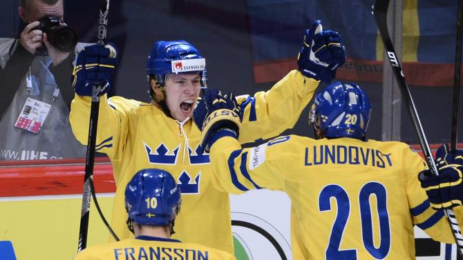 Sweden's Erik Gustafsson, background celebrates scoring a goal during the 2013 Ice Hockey IIHF World Championships gold medal match against Switzerland,  at the Ericsson Globe Arena,   in Stockholm, Sweden,  Sunday, May 19, 2013. (AP Photo/Scanpix Sweden/Claudio Bresciani)  SWEDEN OUT