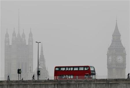 A bus crosses Waterloo bridge in front of the Houses of Parliament during a misty morning in London