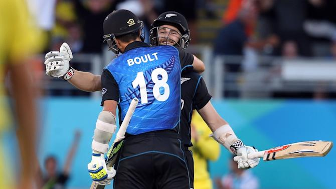 New Zealand's Kane Williamson (R) and Trent Boult celebrate beating Australia during their 2015 Cricket World Cup Pool A match at Eden Park in Auckland on February 28, 2015