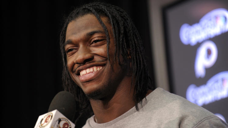 FILE - In this Jan. 2, 2013, file photo, Washington Redskins quarterback Robert Griffin III smiles as he speaks during a news conference following an NFL football practice at Redskins Park in Ashburn, Va. Griffin has won The Associated Press 2012 NFL Offensive Rookie of the Year award, beating out two other sensational first-year quarterbacks, it was announced on Saturday, Feb. 2, 1013. (AP Photo/Susan Walsh, File)