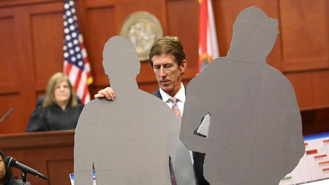 FILE - Defense counsel Mark O'Mara carries life-size cutouts representing George Zimmerman and Trayvon Martin, in the courtroom during closing arguments on the 24th day of Zimmerman's trial at the Seminole County Criminal Justice Center, in Sanford, Fla. on Friday, July 12, 2013. The national conversation over the not guilty verdict shows two sides talking about two different things: either the two minutes when Zimmerman and Martin fought face to face, or the centuries of racial context that many believe caused a senseless death. (AP Photo/Orlando Sentinel, Joe Burbank, Pool)