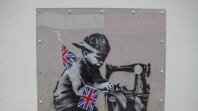 """This is an undated image of an art work from  British artist Banksy made available by Haringey Council Wednesday Feb. 20, 2013. The stencil by the famed, secretive graffiti artist of a young boy sewing Union Jack bunting on an antique sewing machine appeared on the side of a north London bargain store last May. Soon the gritty Turnpike Lane area was drawing art lovers keen to see Banksy's typically cheeky take on the Diamond Jubilee celebrations of Queen Elizabeth II's 60 years on the British throne. Last week it vanished, leaving nothing but a rectangle of exposed brick — only to reappear on the website of a Miami auction house. Listed as """"Slave Labor (Bunting Boy),"""" it is due to be sold Saturday with an estimated price of between $500,000 and $700,000. (AP Photo/Haringey Council)  NO ARCHIVE"""