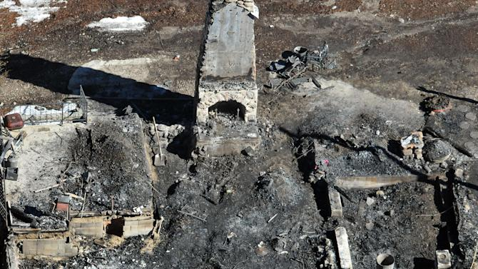 In this aerial photo, law enforcement authorities investigate the charred remnants of a cabin Wednesday, Feb. 13, 2013 in the Angeles Oaks area of Big Bear, Calif. An official briefed on the investigation tells The Associated Press that a wallet with a California driver's license with the name Christopher Dorner has been found in the rubble of a cabin. A charred body was also found inside after a shootout and fire. Authorities believe the remains are those of the former Los Angeles police officer, but they have not been formally identified. (AP Photo/The Sun, John Valenzuela)