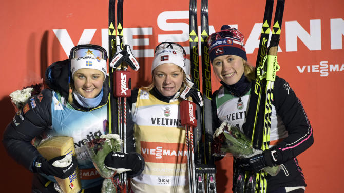 Sweden's second placed Nilsson, Norway's winner Falla and Norway's third placed Haga celebrate after their women's 1.4 km Sprint Classic finals during the FIS Ruka Nordic 2015 in Kuusamo