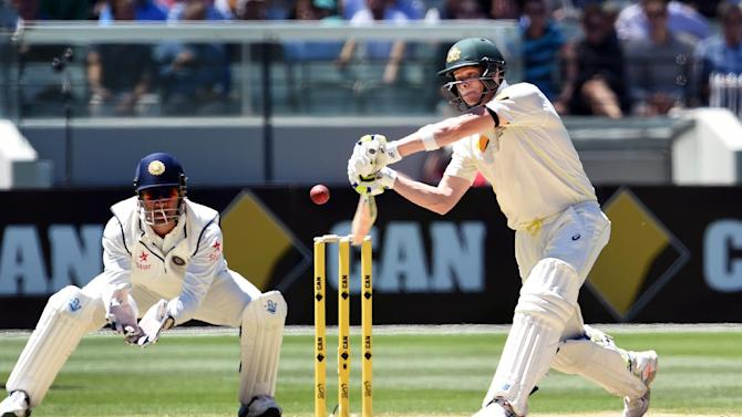 Australia batsman Steve Smith (R) drives a ball as Indian wicketkeeper Mahendra Singh Dhoni watches on during the second day of the third Test match at the Melbourne Cricket Ground (MCG) in Melbourne on December 27, 2014