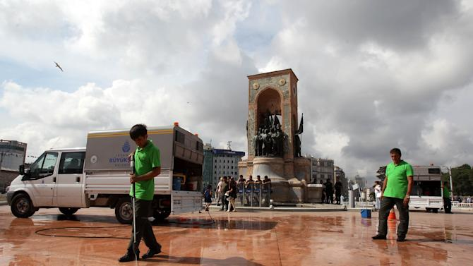 Municipality workers clean the ground from graffiti around the monument of Mustafa Kemal Ataturk, founder of the modern Turkey, at the Taksim Square in Istanbul on Thursday, June 13, 2013. Turkey's government on Wednesday offered a first concrete gesture aimed at ending nearly two weeks of street protests, proposing a referendum on a development project in Istanbul that triggered demonstrations that have become the biggest challenge to Prime Minister Recep Tayyip Erdogan's 10-year tenure. (AP Photo/Thanassis Stavrakis)
