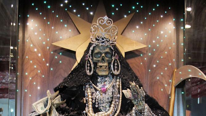 In this Feb. 12, 2013 photo, an altar to La Sante Muerte run by Arely Vazquez Gonzalez, a Mexican immigrant and transgender woman, is shown inside a Queens, NY apartment.  La Santa Muerte, an underworld saint most recently associated with the violent drug trade in Mexico, now is spreading throughout the U.S. among a new group of followers ranging from immigrant small business owners to artists and gay activists. In addition to showing up at drug crime scenes, the once-underground icon has been spotted on passion candles in Richmond, Va. grocery stores. The folk saint's image can be seen inside New York City apartments, in Minneapolis religious shops and during art shows in Tucson, Ariz.  (AP Photo/Russell Contreras)
