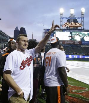 Cleveland Browns quarterback Johnny Manziel waves to fans before the Cleveland Indians play the Boston Red Sox in a baseball game, Wednesday, June 4, 2014, in Cleveland. (AP Photo/Tony Dejak)