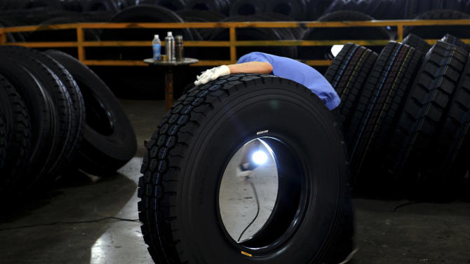 In this photo taken Tuesday, May 29, 2012, a Chinese worker inspects a tire at the Hangzhou Zhongce Rubber Company, one of China's largest tire makers, in Hangzhou in eastern China's Zhejiang province. China is rolling out a mini-stimulus to fight its economic slump but is moving cautiously after its massive response to the 2008 global crisis left a painful hangover of inflation and debt.(AP Photo) CHINA OUT