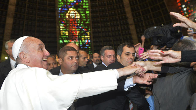 "Pope Francis greets Argentines inside the Metropolitan Cathedral in Rio de Janeiro, Brazil, July 25, 2013. Francis added a last-minute tweak to his busy schedule, meeting with pilgrims from his native Argentina at Rio's cathedral Thursday afternoon. He told the youngsters to get out into the streets and spread their faith, saying that a church that doesn't go out and preach becomes a simple NGO, or nongovernmental organization. ""And the church cannot be an NGO!"" he said to applause. (AP Photo/Luca Zennaro, Pool)"