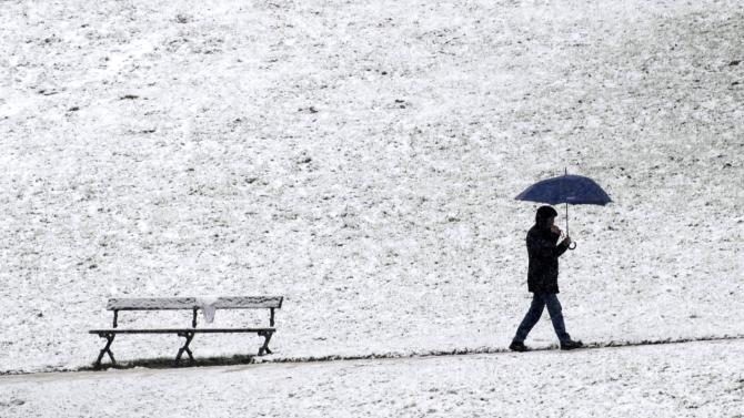A man walks at the Bois de la Cambre during the first snowfall in Brussels