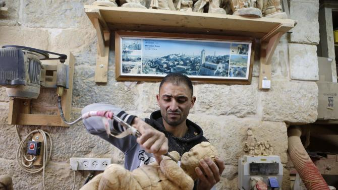 A Palestinian sculptor carves a model of baby Jesus from a piece of olive wood in a workshop, ahead of Christmas in the West Bank city of Bethlehem