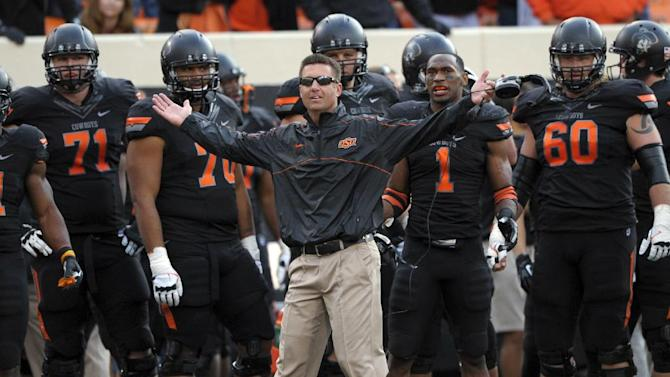 """In this Oct. 27, 2012, file photo, Oklahoma State coach Mike Gundy, center, questions an official's call denying Oklahoma State a touchdown during the second half of an NCAA college football game against TCU in Stillwater, Okla. An NCAA committee passed a proposal Wednesday, Feb. 12, 2014, that would allow defenses time to substitute between plays by prohibiting offenses from snapping the ball until 29 seconds are left on the 40-second play clock. """"The 10-second rule is like asking basketball to take away the shot clock - Boring!"""" Gundy tweeted Thursday. """"It's like asking a blitzing linebacker to raise his hand."""""""