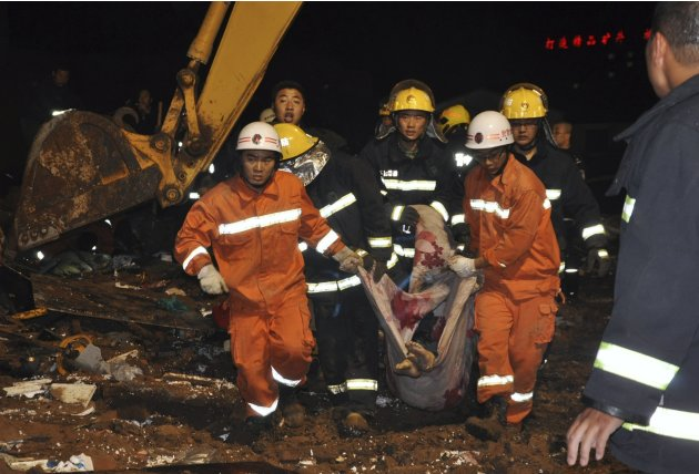 Rescue workers carry a victim after a makeshift building collapsed under heavy rainfall in Jinzhong