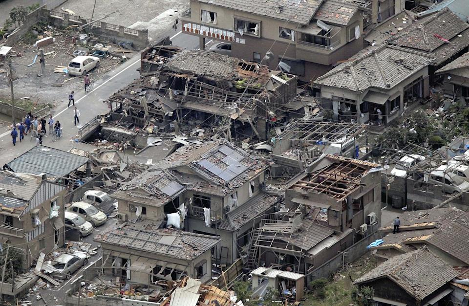 People walk near damaged buildings after a tornado struck Tsukuba city, northeast of Tokyo, Sunday, May 6, 2012. The tornado tore through the area, injuring at least 30 people, destroying dozens of homes and leaving thousands more without electricity. (AP Photo/Yomiuri Shimbun, Yoko Miwa) JAPAN OUT