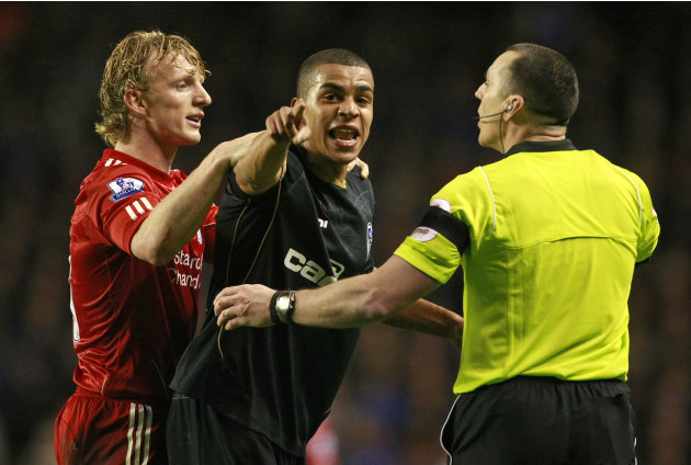Oldham Athletic's Tom Adeyemi, center, is calmed by Liverpool's Dirk Kuyt, left, and referee Neil Swarbrick during their FA Cup third round soccer match at Anfield, Liverpool, England, Friday Jan. 6, 