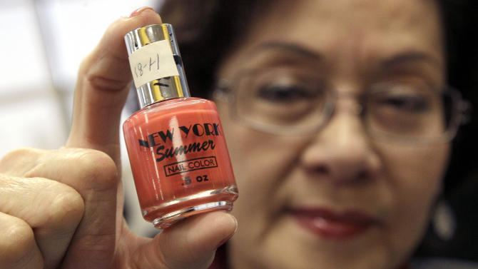 Loann Tran, co-owner of Happy Nails in Salinas, Calif., holds up a bottle of nail polish that was tested and found to contain toluene and formaldehyde, despite being labeled as free of those toxic chemicals, after a news conference at the Laney College School of Cosmetology in Oakland, Calif., Tuesday, April 10, 2012. Some nail polishes commonly found in California salons and advertised as free of a so-called ìtoxic trioî of chemicals actually have high levels of agents known to cause birth defects,according to state chemical regulators. (AP Photo/Jeff Chiu)