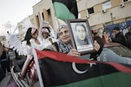 An Libyan woman holding a portrait of a dead relative parades during celebrations in the streets of the eastern city of Benghazi. Libya began celebrating on Friday the first anniversary of the uprising against Moamer Kadhafi, with fireworks and slogans, even as its new leader vowed to act firmly against further instability
