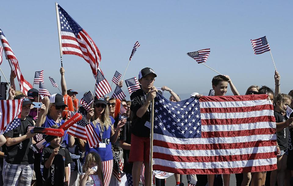 Fans of Oracle Team USA wait for the arrival of the crew at a dock out show prior to the 12th race of the America's Cup sailing event against Emirates Team New Zealand Thursday, Sept. 19, 2013, in San Francisco. (AP Photo/Ben Margot)