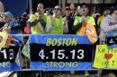 Race fans from left, Andrew Lembecke, of Chicago, Brandon Petrich of Fargo, N.D, Marlene Youngblood of Louisville, Ky, and Bill Januszewski cheer near the finish line at the 118th Boston Marathon Monday, April 21, 2014 in Boston. (AP Photo/Robert F. Bukaty)