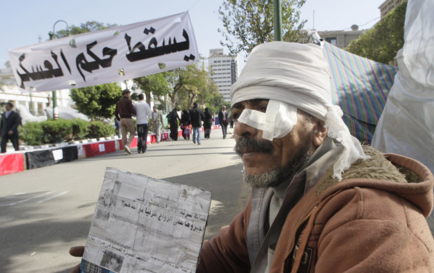 "Mohammed Hennaway, who was injured during recent clashes with security forces, sits in front of his tent during a protest demanding the ruling military council to step down in front of the cabinet office in Cairo, Egypt, Sunday, Dec. 4, 2011. The banner, in Arabic, reads ""down with military rule."" (AP Photo/Amr Nabil)"