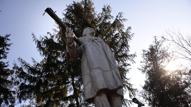 In this Wednesday Nov. 5, 2014 photo, a statue of the Soviet founder Vladimir Lenin with a grenade launcher fixed in a hand is situated at one of the Cossacks check-points at Miusinsk, Eastern Ukraine. As armed pro-Russian separatists were seizing one town after another in eastern Ukraine, groups of Cossacks in early May crossed from southern Russia to occupy territories along the border. They claimed they did so to defend the interests of the native Russian-speaking population.  (AP Photo/Mstyslav Chernov)