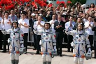 <p>Mission commander Jing Haipeng (R) with fellow astronauts Liu Wang (C) and Liu Yang, China's first female astronaut, wave to the crowd prior to boarding the Shenzhou-9 spacecraft on June 16. The crew's main task during their 13-day mission is to carry out China's first manual space docking.</p>