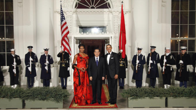 FILE - In this Jan. 19, 2011 file photo, U.S. President Barack Obama and first lady Michelle Obama pose with China's President Hu Jintao at the North Portico of the White House in Washington. In the simplistic narrative of U.S. presidential politics, China is a Hollywood villain, a monetary cheat that is stealing American jobs. But in the debate Tuesday night, Oct. 16, 2012 the one-dimensional caricature offered up by Obama and Republican challenger Mitt Romney obscures the crucial reality of U.S.-China relations: For all the talk about getting tough on Beijing, the U.S. and China are deeply entwined, defying easy solutions to the friction and troubles that beset their relations. (AP Photo/Pablo Martinez Monsivais, File)