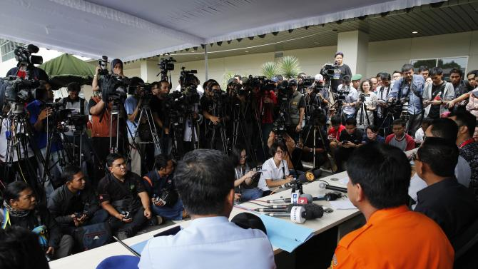 Journalists crowd during news conference on search and locate operation for missing AirAsia flight QZ8501, at Juanda International Airport, Surabaya