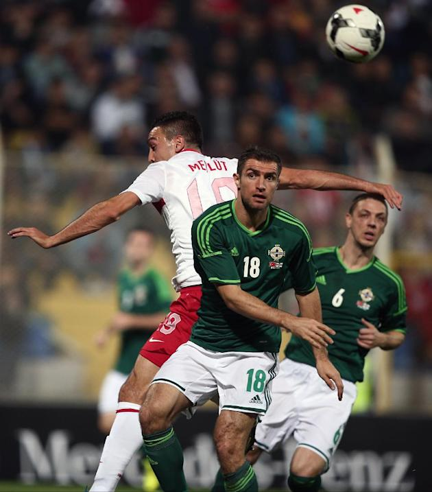 Turkey's Mevlut Erdinc, left, and Aaron Hughes of Northern Ireland fight for the ball during their friendly soccer match in Adana, Turkey,  Friday, Nov. 15, 2013. (AP Photo)