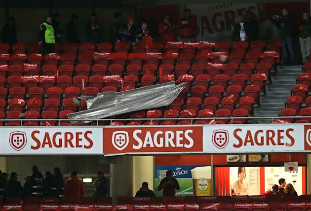 People look at a sheet of aluminum that fell on the stands after people started leaving their seats before the start of the Portuguese league soccer match between Benfica and Sporting Sunday, Feb. 9 2