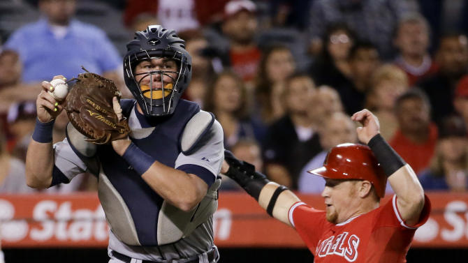 Detroit Tigers catcher James McCann, left, forces Los Angeles Angels' Kole Calhoun out at home on a ball hit by Chris Iannetta during the sixth inning of a baseball game in Anaheim, Calif., Thursday, May 28, 2015. (AP Photo/Chris Carlson)