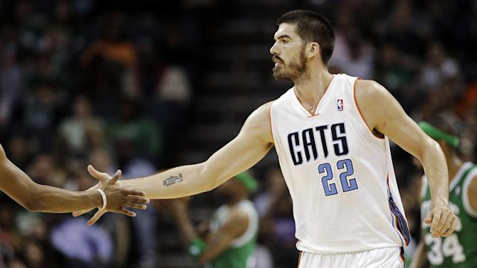 Charlotte Bobcats' Byron Mullens (22) is congratulated by a teammate after making a basket against the Boston Celtics during the second half of an NBA basketball game in Charlotte, N.C., Monday, Feb. 11, 2013. The Bobcats won 94-91. (AP Photo/Chuck Burton)
