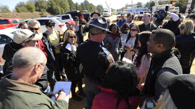 Alabama state trooper Kevin Cook, center right, is surrounded by members of the media following a news conference, Saturday, Feb. 2, 2013, in Midland City, Ala. Authorities said they still have an open line of communication with an Alabama man accused of abducting a 5-year-old child and holding him hostage in a bunker since Tuesday, Jan. 29. Sheriff Wally Olson said Saturday that Jimmy Lee Dykes has told them that he has blankets and an electric heater in the bunker. (AP Photo/al.com, Joe Songer) MAGS OUT.