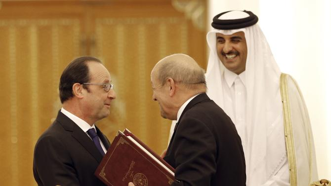 French President Francois Hollande talks with French Defense Minister Jean-Yves Le Drian as Qatar's Emir Sheikh Tamim bin Hamad Al-Thani looks on at the Diwan Palace in Doha