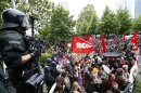 """Riot police stand guard in front of protesters during an anti-capitalism """"Blockupy"""" demonstration in Frankfurt"""